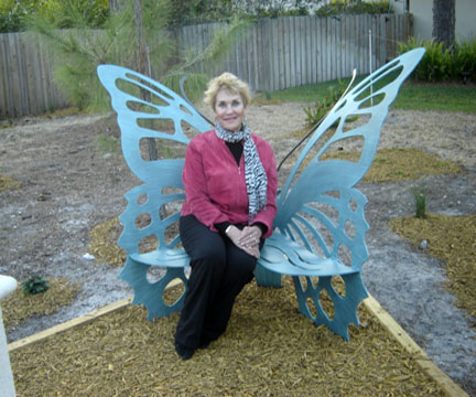 M..eE. DePalma sitting on the butterfly bench in the park named after her.